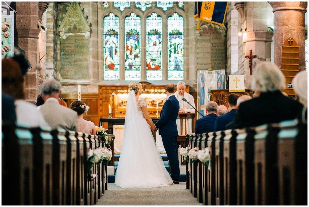 bride and groom stood at the alter looking and facing each other