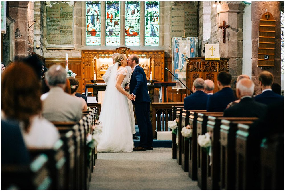 bride and groom sharing their first kiss at the altar