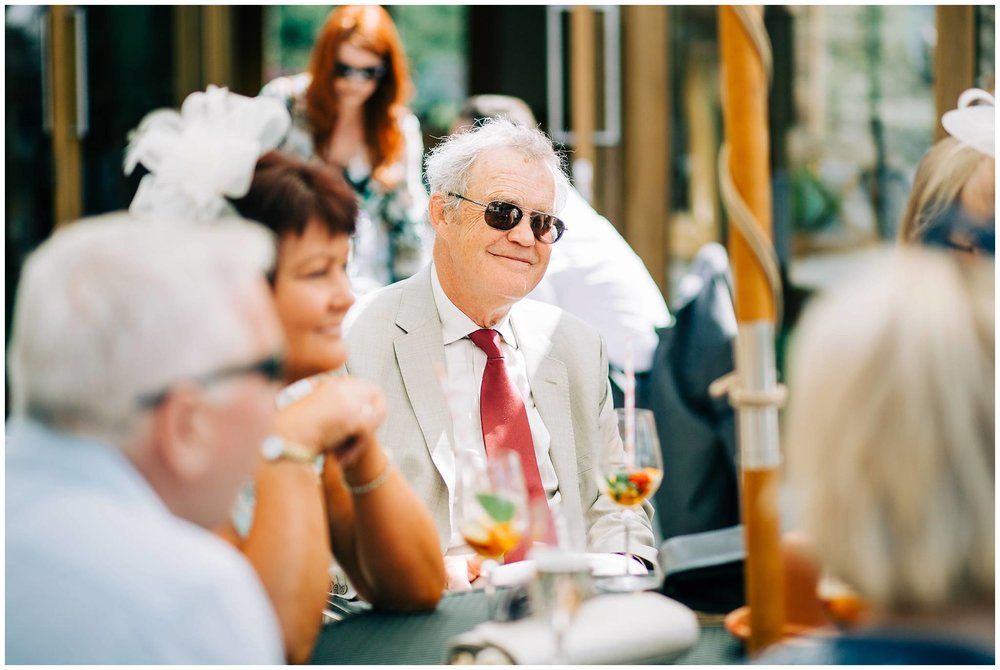 older gentleman wear sunglasses and a red tie smiling to fellow guests