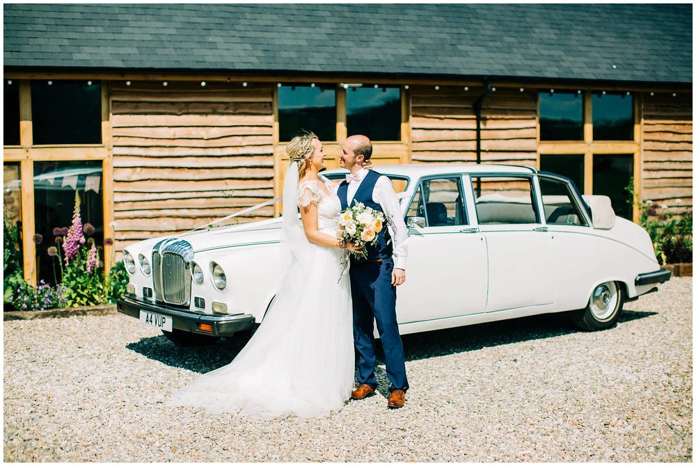 bride and groom kissing and cuddling in front of the white wedding car with tower hill barns in the background