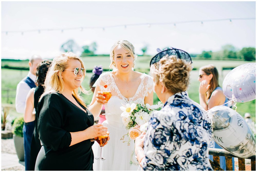 bride holding a glass of pims is talking and smiling at the mother of the bride