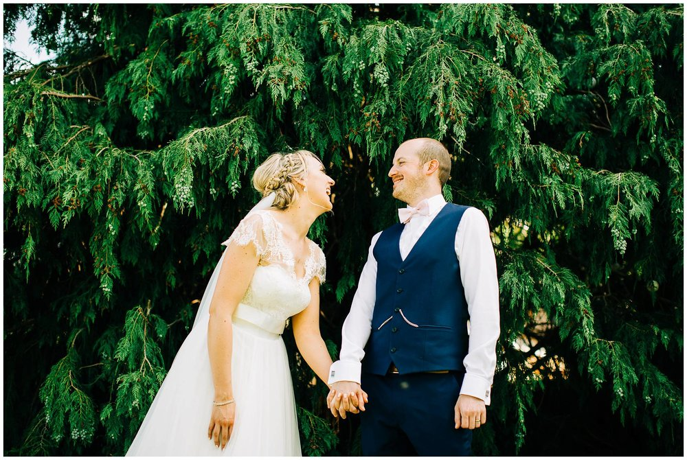 baride and groom laughing with a towering conifer  behind them