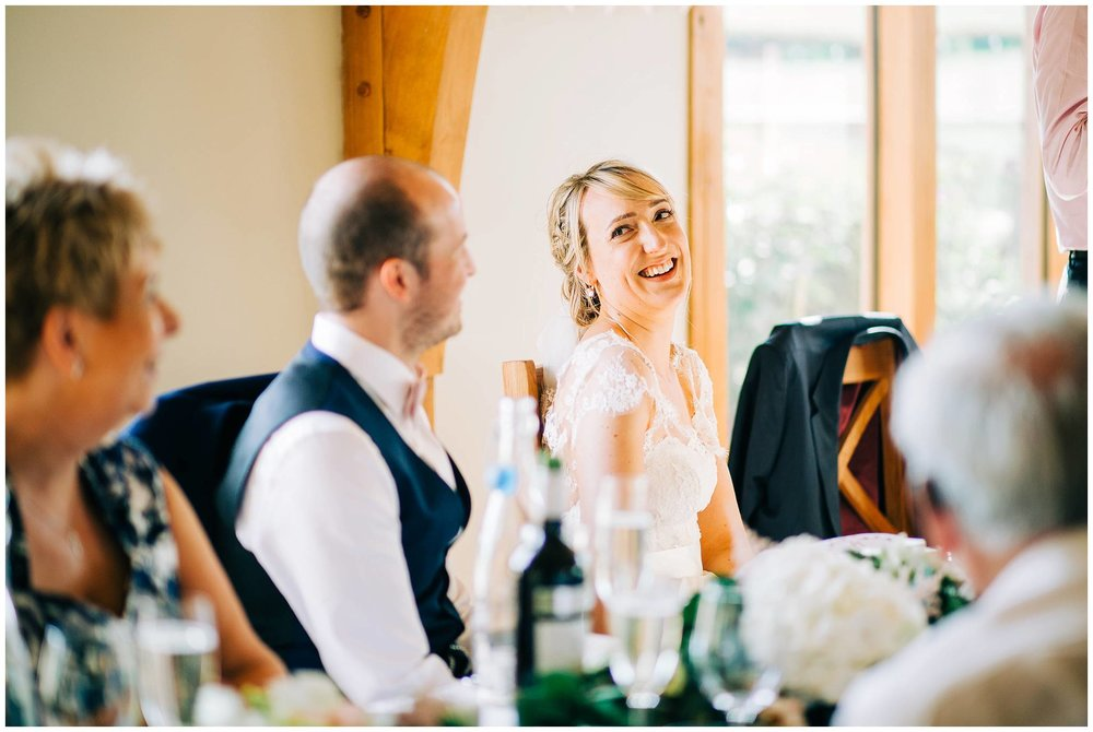 bride looking over her shoulder to the groom whilst sat at the top table
