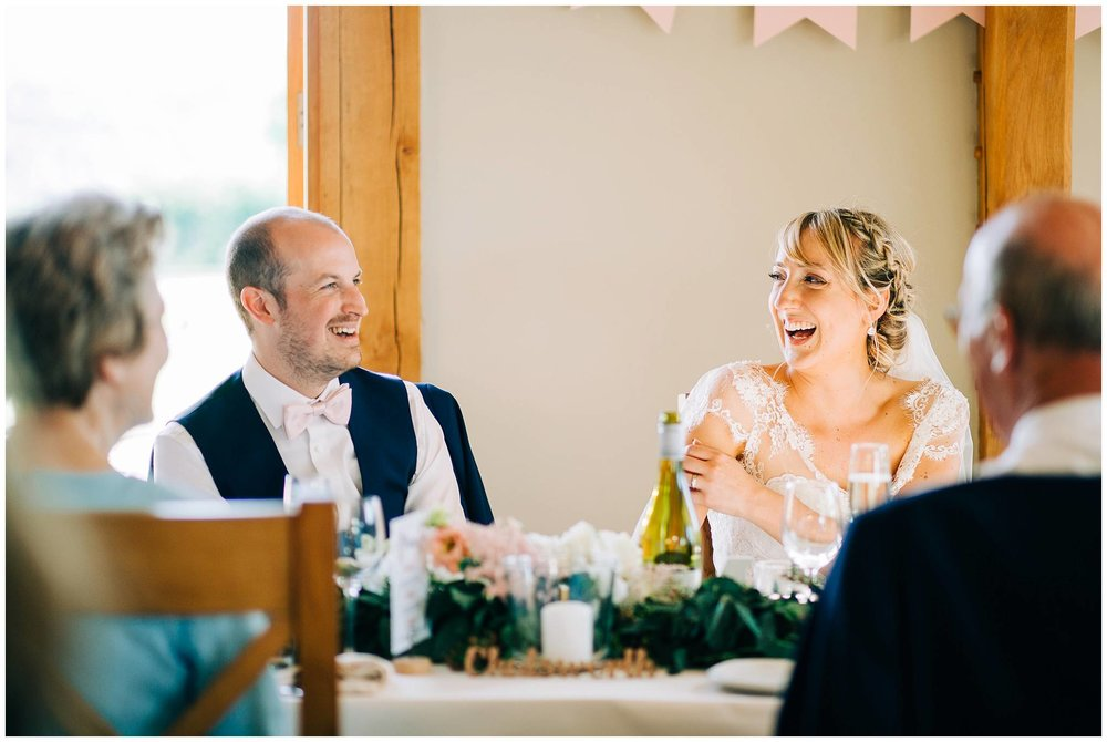 bride and groom sat laughing with each other at the top table during speeches