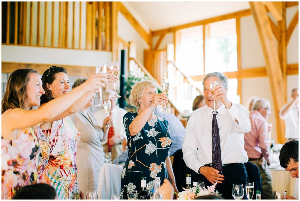 a group of guests stand up from their table to make a toast with their glasses