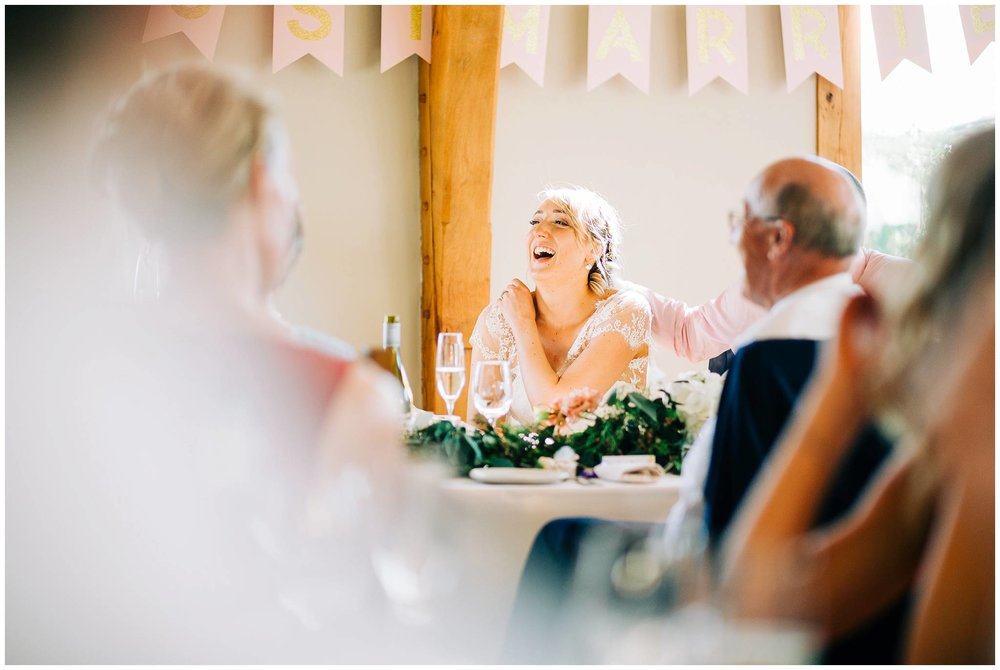 the bride is laughing at the best man speech while her dad places his hand on her shoulder