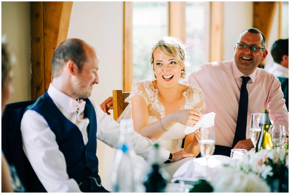 the bride is laughing and looking back at the groom after viewing superimposed images of the grooms head on female celebrities bodies