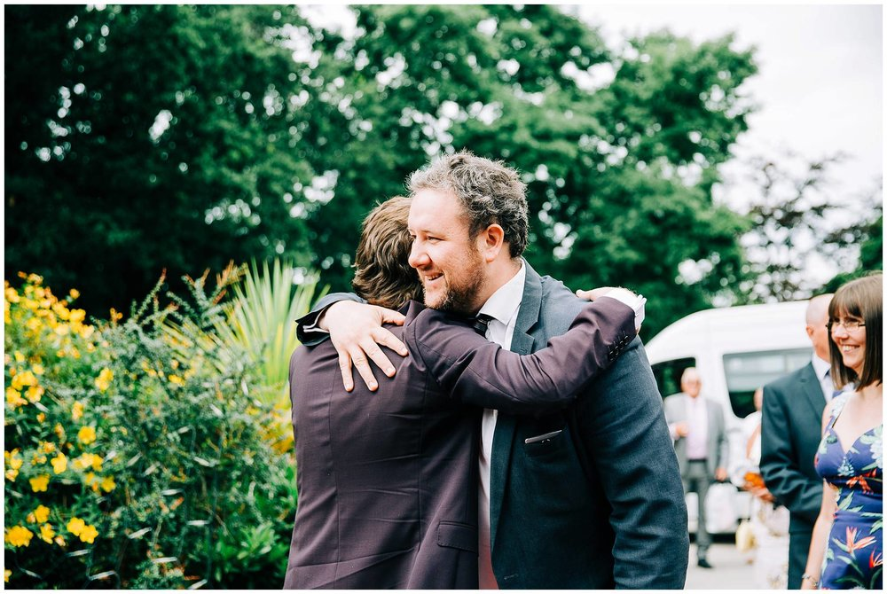 groom hugging an arriving wedding guest