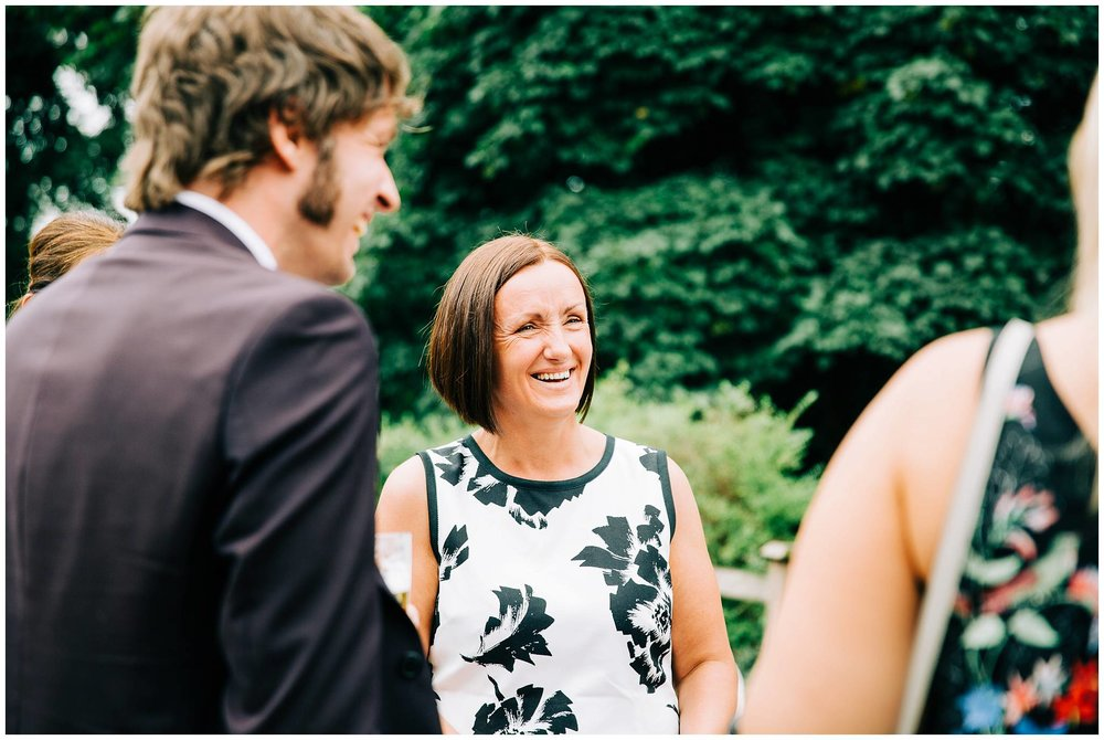 groom talking to guest with short bobbed hair with white and black leafy top