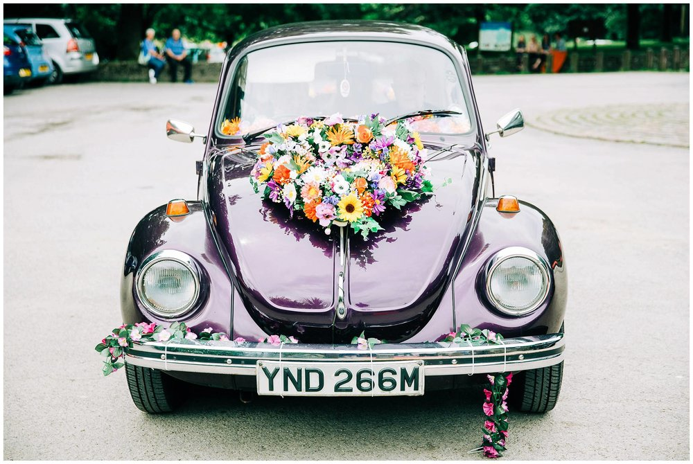 vintage purple VW beetle with floral heart shaped arrangemen on front