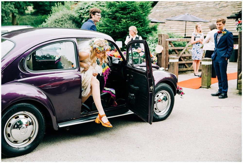 bride steps out of vintage purple VW beetle