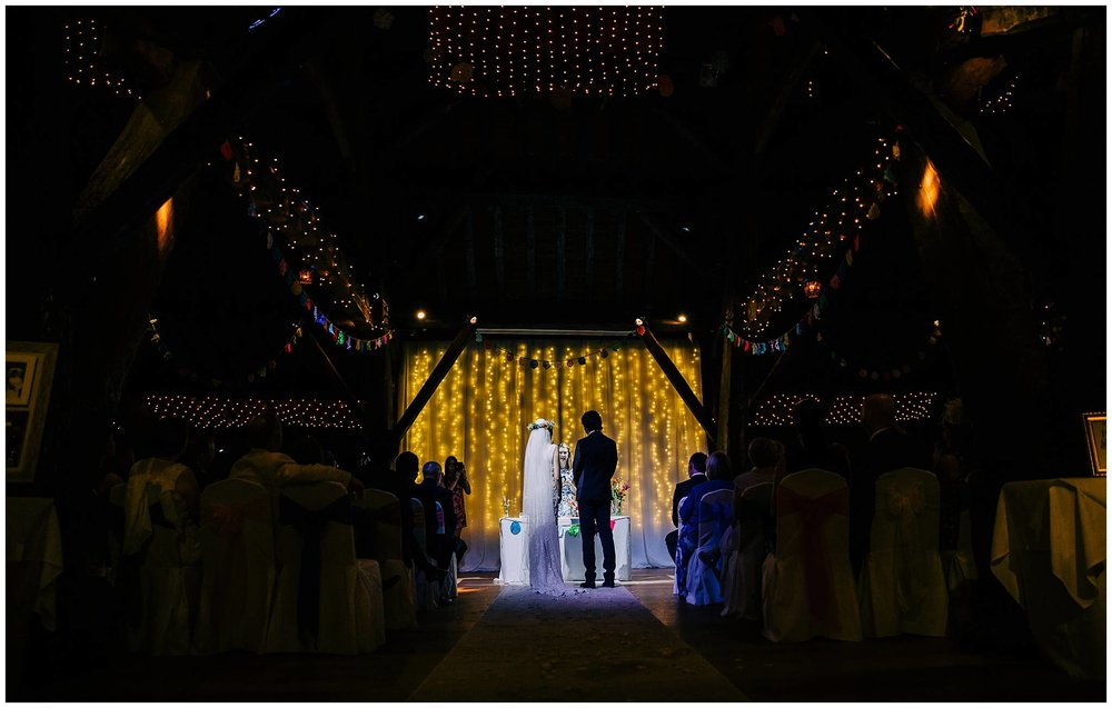 bride and groom stood in aisle lit up by a spot light