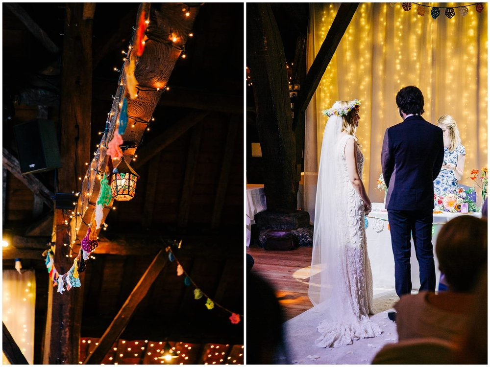 briode and groom stood in aisle and an exposed beam covered in fairy lights and crochet bunting