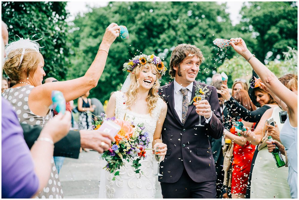 bride and groom laughing whilst getting a face full of confetti