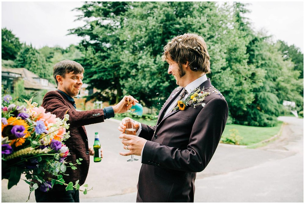 guest throwing a cone of confetti on groom