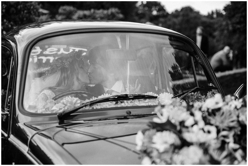 bride and groom sharing a kiss in the front of VW beetle