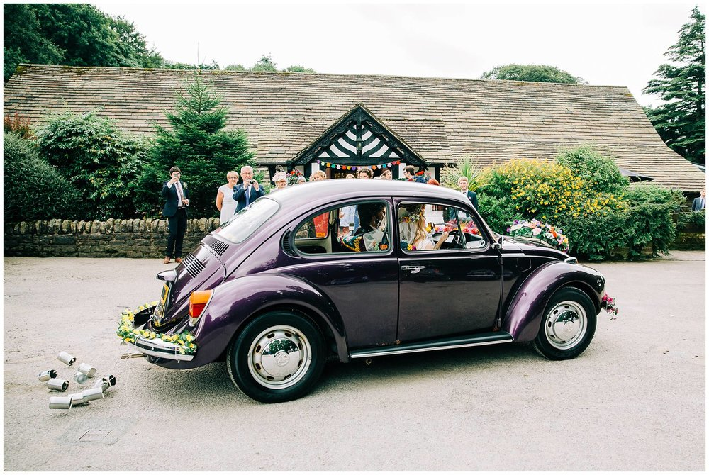 bride driving vintage VW beetle draggin tin cans behind