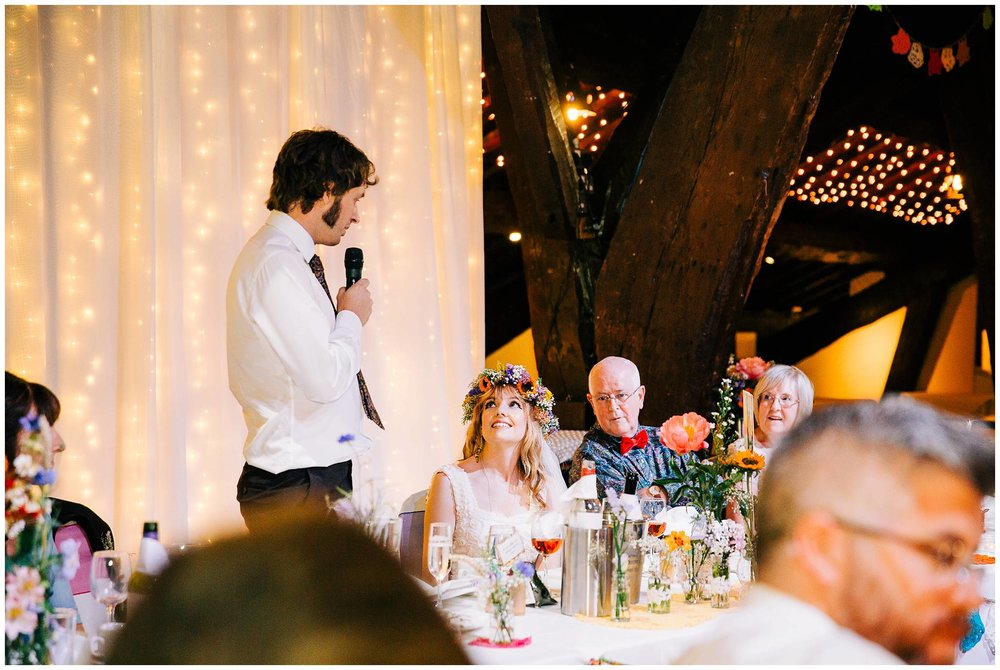 groom stood looking down at bride during his speech