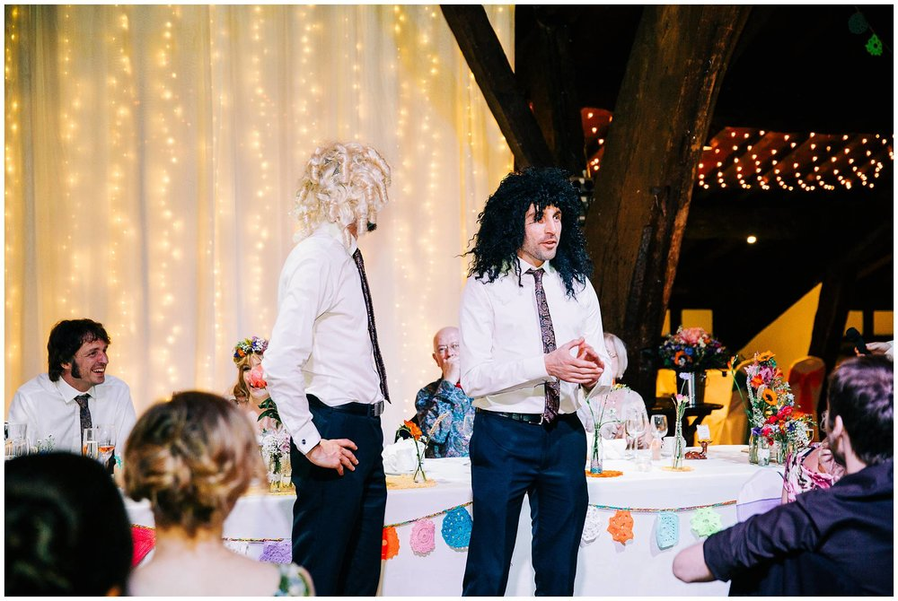 best men wear big curly wig during wedding speeches