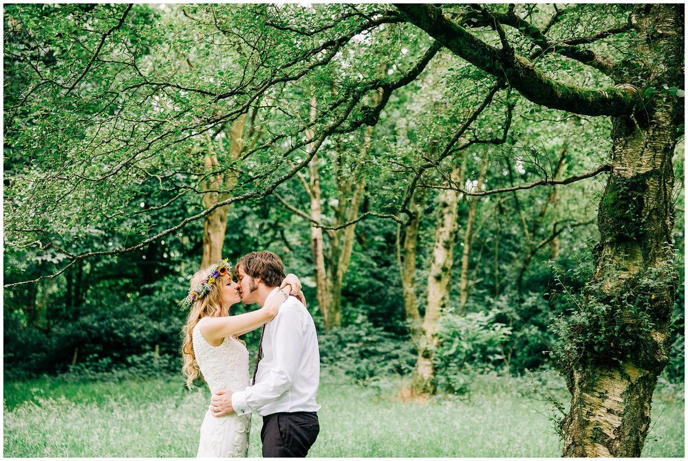 bride nd groom share a kiss under large tree branch