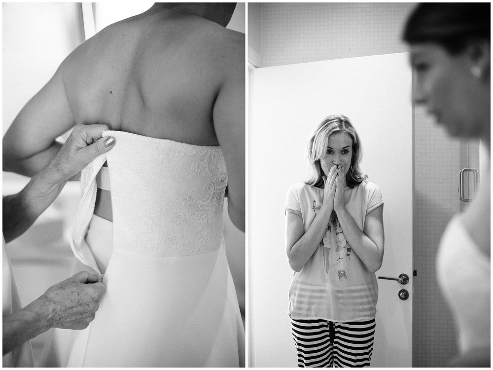 mother of the bride zipping her dress up and the emotional reaction from her sister