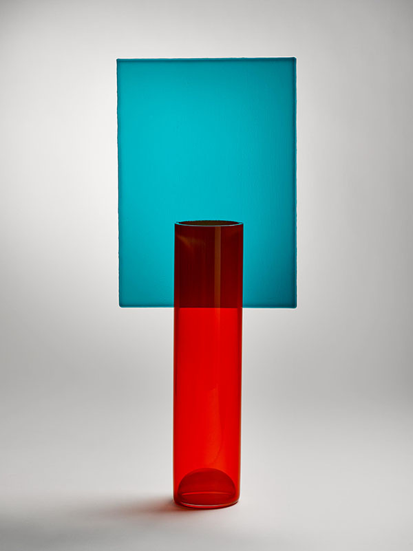 A hand-blown cylindrical vase made of red coloured glass is juxtaposed with a square sheet of blue glass fitted vertically above the vase. The vase evokes the style of the Memphis Group, with whose members  Pierre Charpin  worked in his early career.