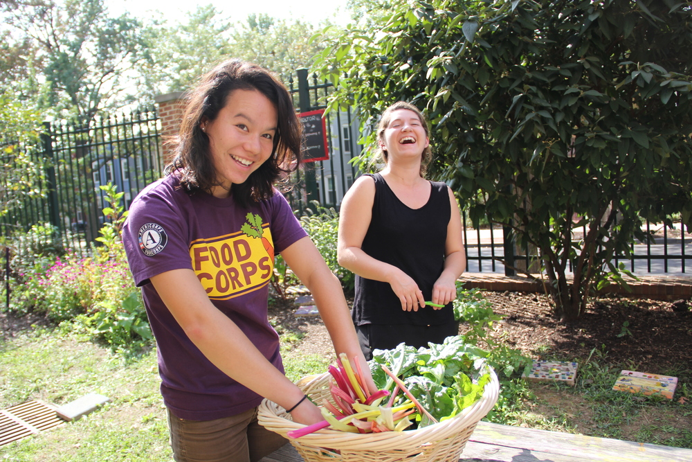 Mika and Hannah G. checking out the garden harvest. (Photo by Hannah Cather)