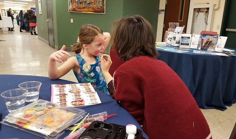 FRH's Community Outreach Coordinator Jessica Schatz paints a child's face pink.