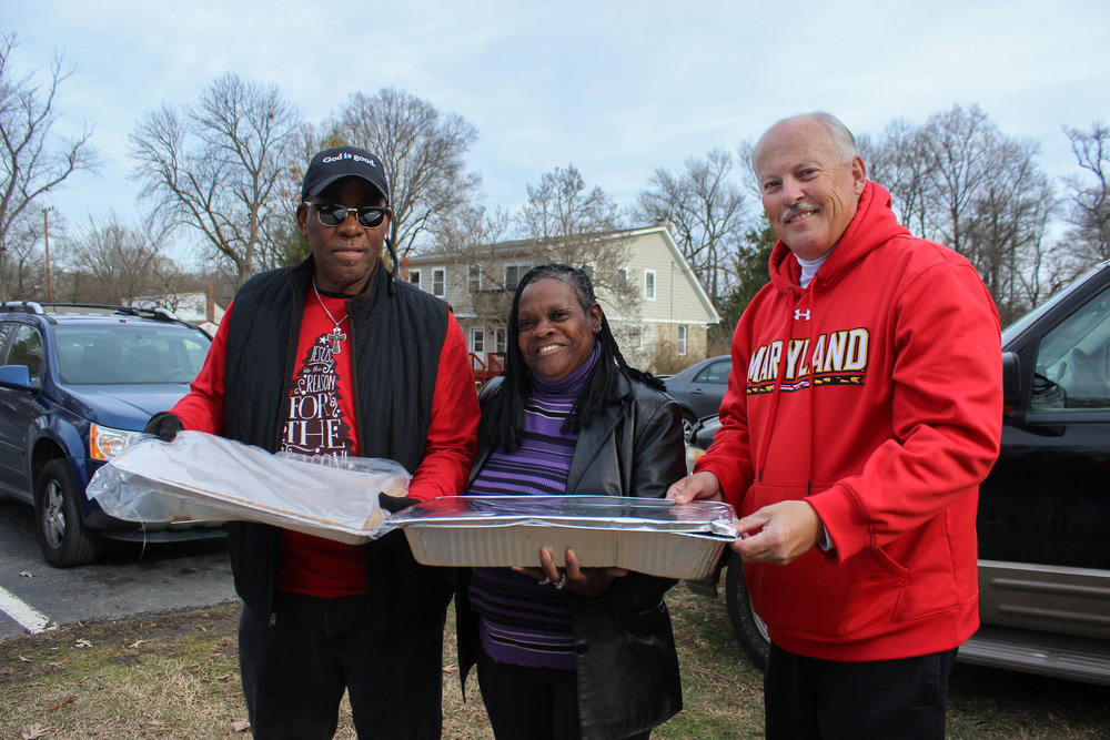 Eric and Pastor Ben pose with community member Linda, holding trays of recovered food from University of Maryland's campus.