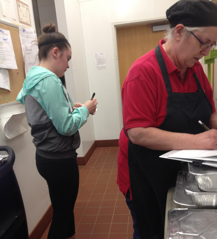 Student Megan Feerick (left) and Aramark employee MaryAnn (right) weighing the food that will be given to the Vermillion Welcome Table.