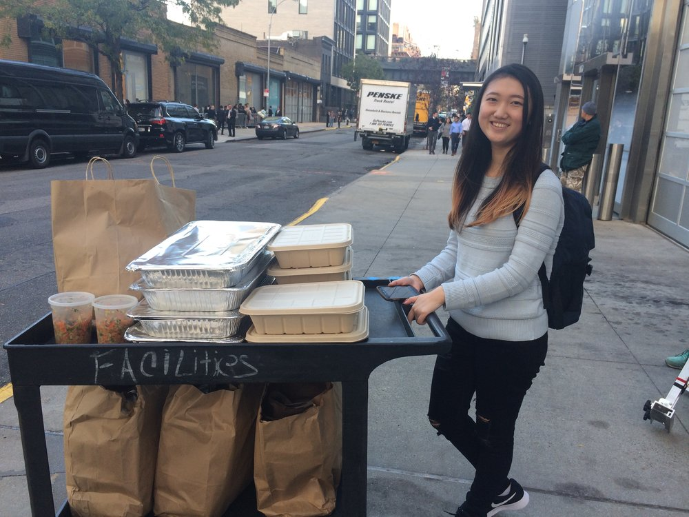 Lanie, NYU student, wheeling extra food from NationSwell Fall Summit for donation to The Bowery Mission.