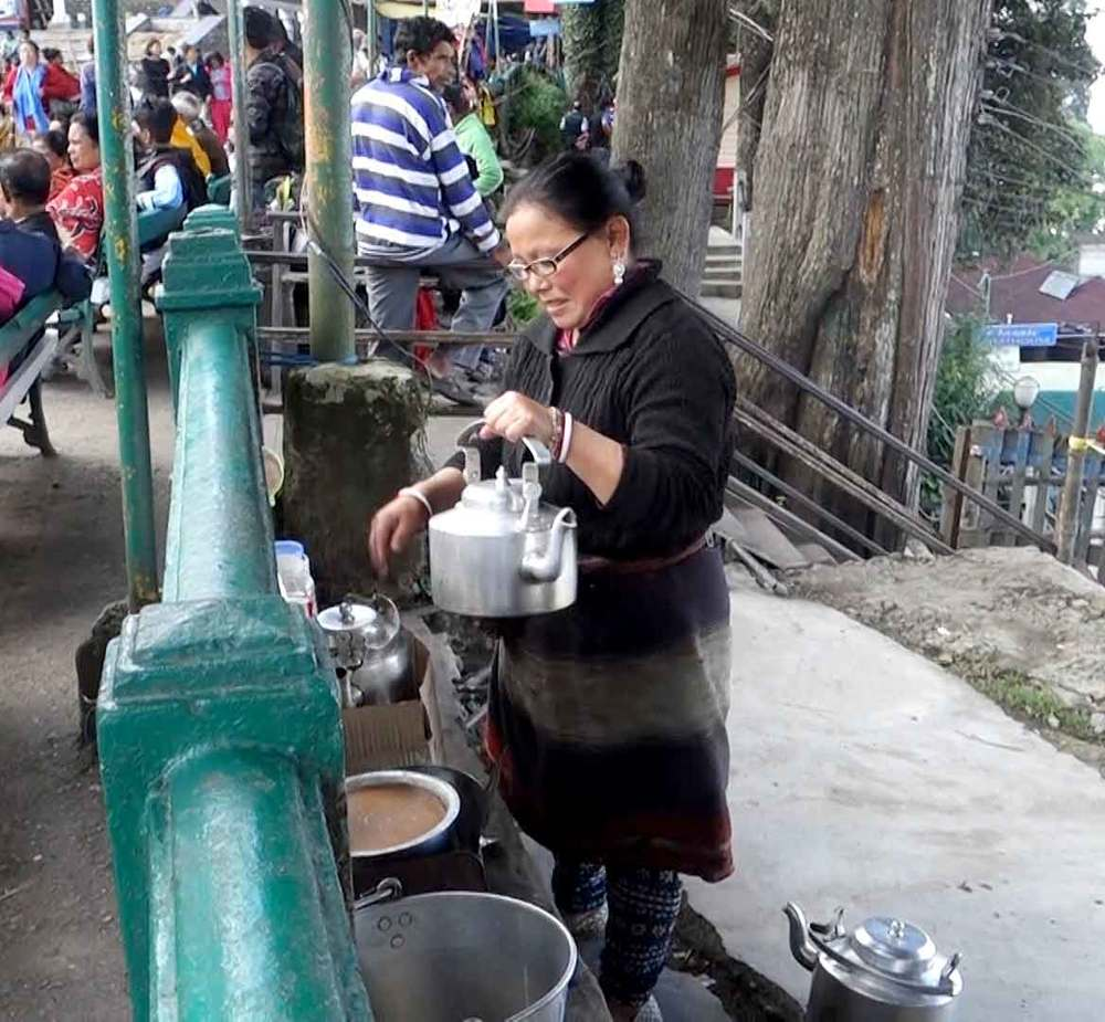 Woman serving chai in the town square.