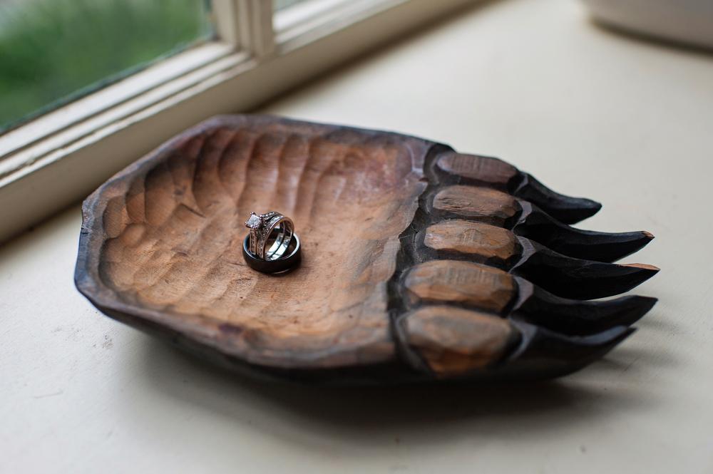 wedding rings in a black bear paw dish