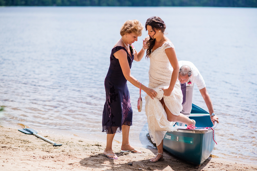 mother helping daughter out of canoe adirondack wedding