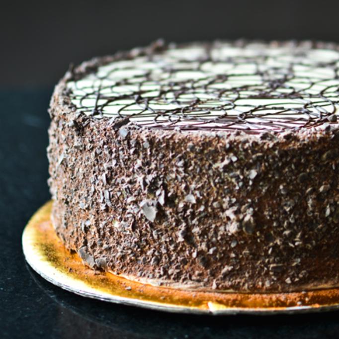 MOCCHA Queque de chocolate relleno de glase de chocolate con cobertura de crema de mantequilla con café y ralladura de chocolate semi-amargo.