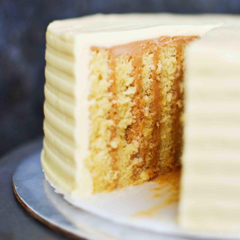 SINFONIA Queque de coco relleno de mousse de dulce de leche y lustre de queso crema.