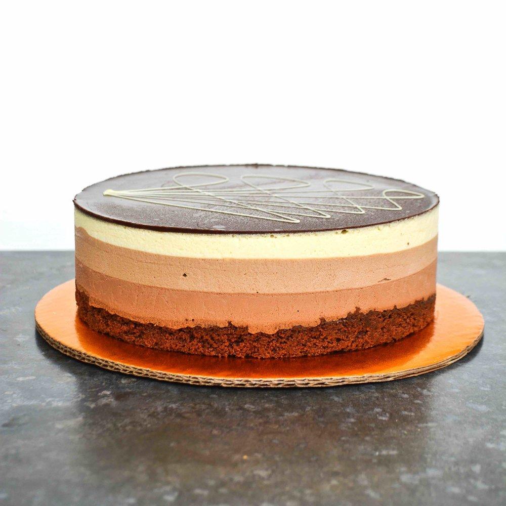 MOUSSE DE MARQUÉS Mousse de capas de chocolate semi-amargo, de leche y blanco con base de torta de chocolate, cubierto con una capa de chocolate.