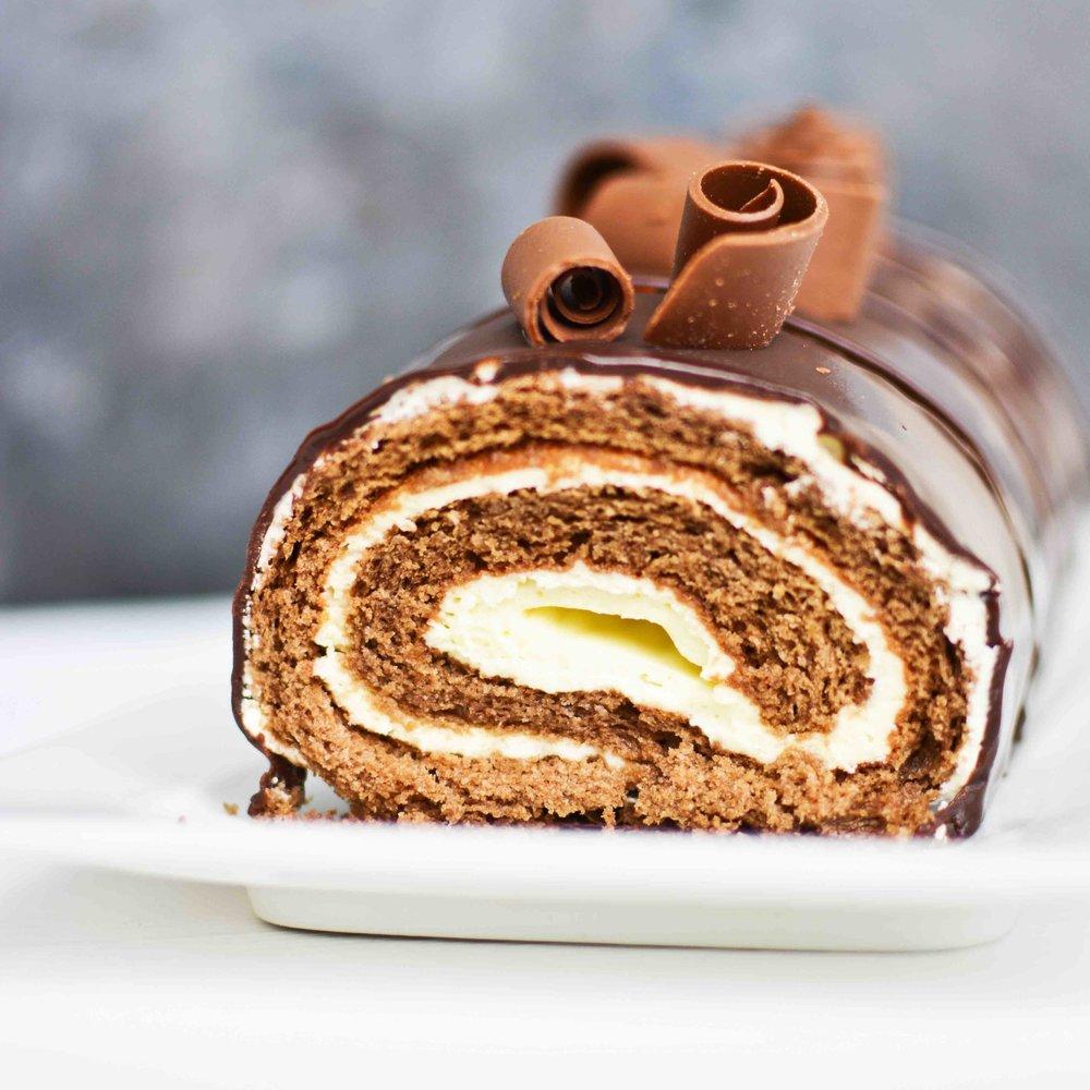ARROLLADO DE CHOCOLATE Queque de chocolate relleno de mousse de chocolate blanco y glaseado de chocolate.