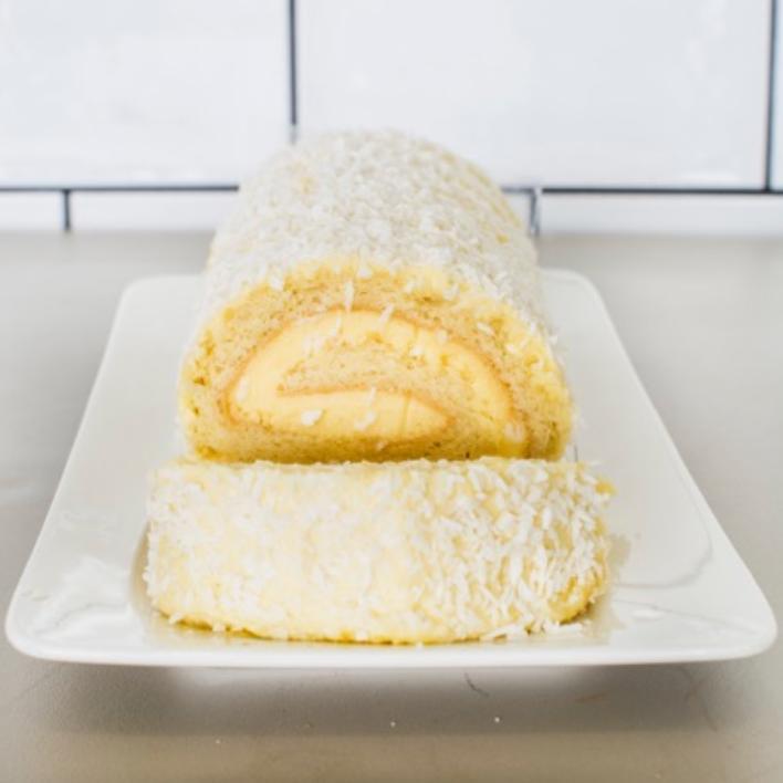 ARROLLADO DE LIMÓN Queque de limón relleno de mousse de limón con cobertura de queso crema y coco.
