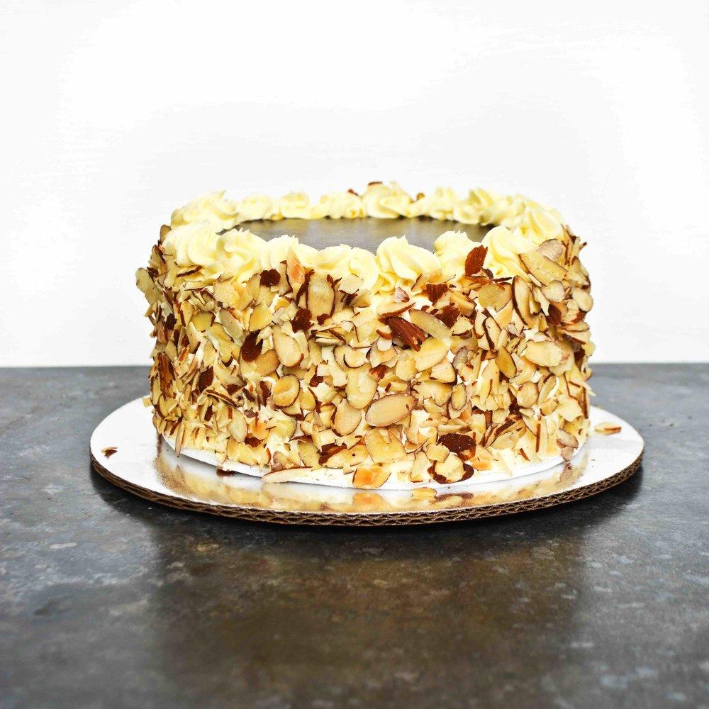 BOSTON CREAM PIE Queque de vainilla, relleno con crema pastelera, cubierto con crema de mantequilla y almendra, con una capa de glase de chocolate.