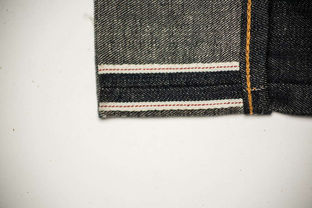 """During the weaving of some denim, the edge is finished off with what is called """"selvedge"""". This produces a clean, luxurious finish on the denim, and also strongly discourages unraveling of the denim. Think of it as a """"stripe of longevity""""."""