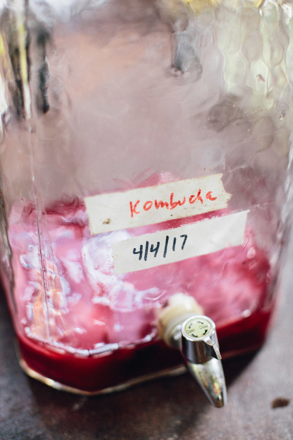 """Kombucha, after straining the previous batch. The """"mother"""" left in the jug, awaits the next fresh batch of hibiscus-steeped water & sugar."""