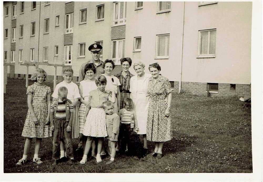 Our extended family in front of our quarters in Landstuhl, Germany, 1960. My father is wearing his hat. I'm on the left, dressed up in saddle shoes.