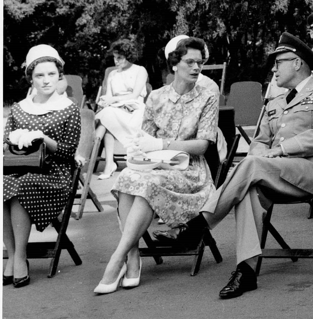 The author's mother, wearing glasses and proper attire, at a public event.