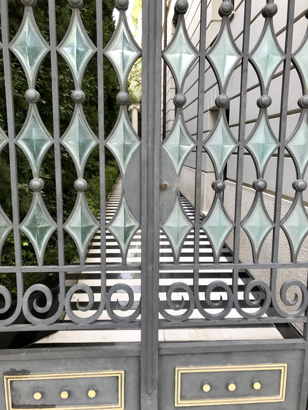 Cast glass set in a decorative and functional gate guarding a black and white striped marble side walk.