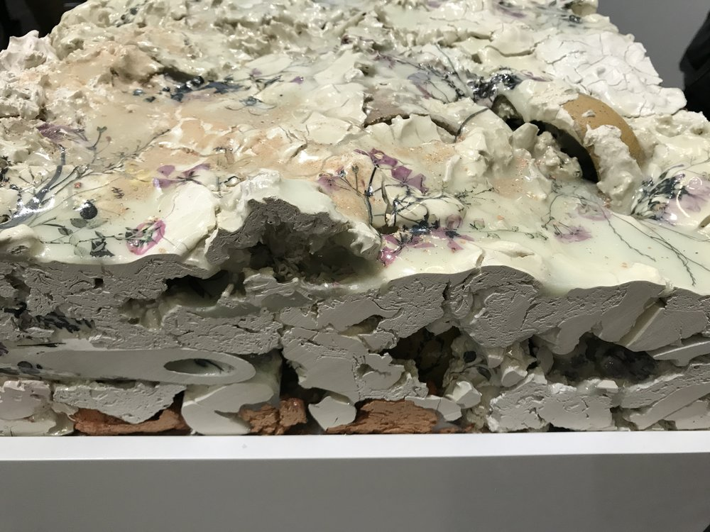 A thick layered ceramic chunk is part of the installation.