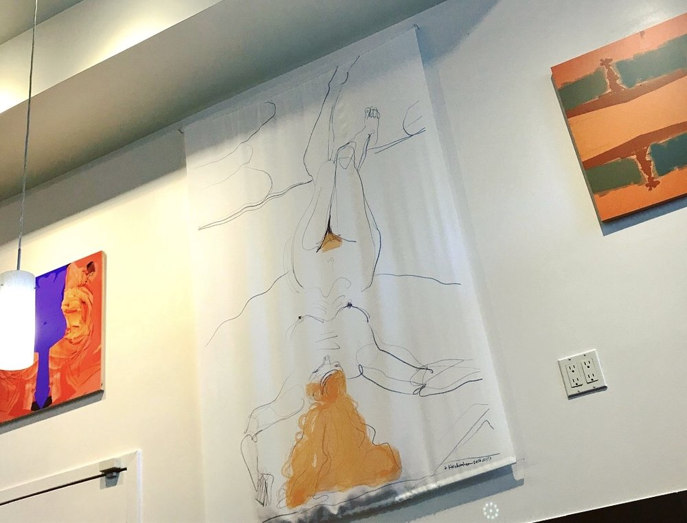 """One of the many high walls at Secret Agent Salon in SF's Pacific Heights, where I was invited to have a spring 2018 solo show. In the center is Red Hair Curly and Straight, Reclining, surrounded by two of my more abstract works that deal with mirror images. On the right is """"Bay of Bengal Sunset"""", a digital photo / paint collage with no drawings. On the left is """"Filled with Roses"""" another figurative collage."""