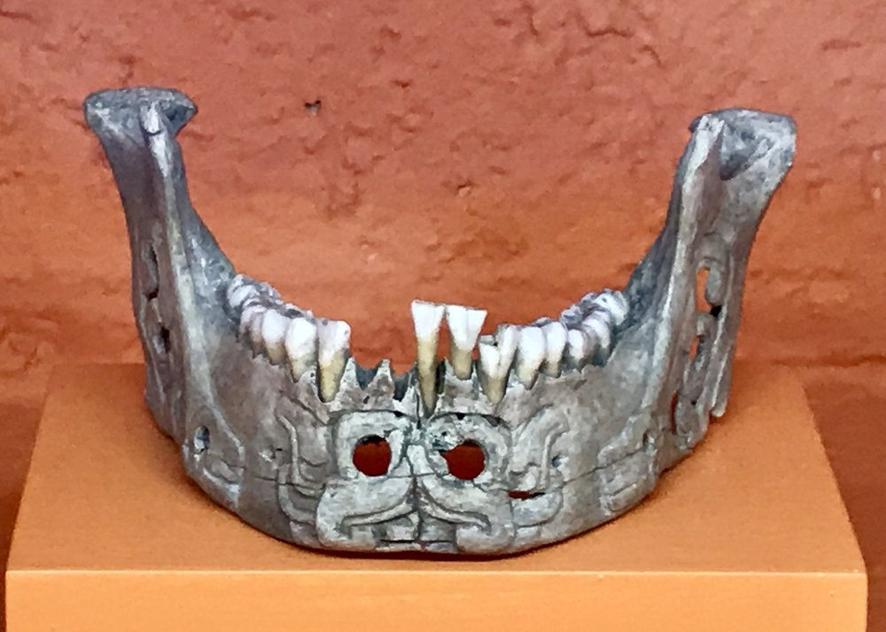 An ornamental carved jaw bone painted silver! Most ceremonial objects like these were buried in the crypts.