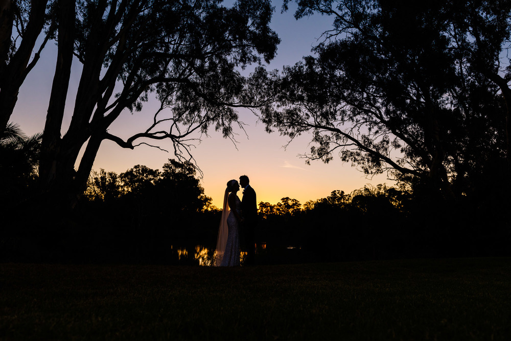 Sunset silhouette of the bride and groom by the river at Perricoota Station