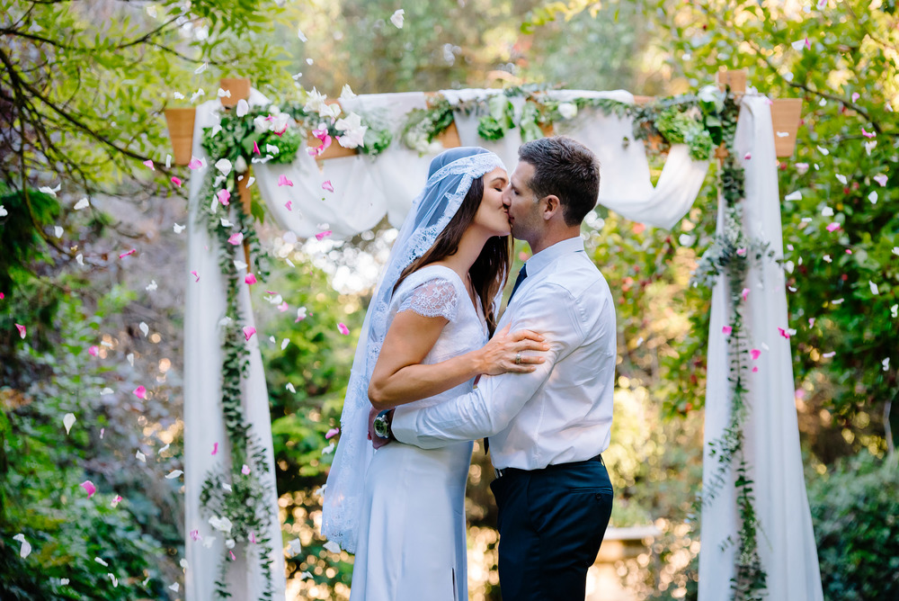 Carly and Daniel kissing in front of their amazing arbour